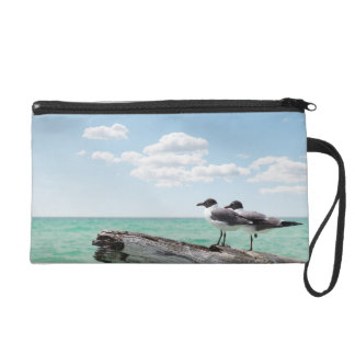 Two seagulls sitting on a dead tree sticking out wristlet