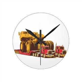 Two Semi Big Trucks carrying a Huge Mining Truck Round Clock