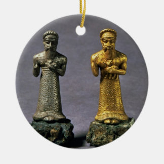 Two statuettes of men carrying offerings of goats, round ceramic decoration