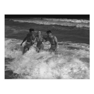Two young men and woman playing in wave B&W Postcard