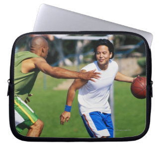 Two young men playing basketball laptop sleeve