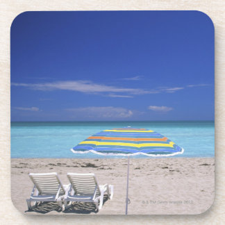 Umbrella and two lounge chairs on beach, Miami Coaster