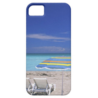 Umbrella and two lounge chairs on beach, Miami iPhone 5 Cover