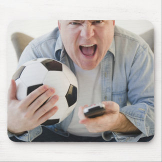 USA, Jersey City, New Jersey, man holding remote Mouse Mat