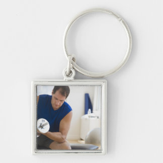USA, New Jersey, Jersey City, Mature man lifting Silver-Colored Square Key Ring
