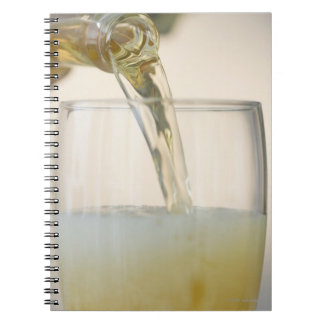 USA, New Jersey, Jersey City, pouring beer into Spiral Notebook
