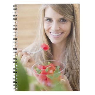 USA, New Jersey, Jersey City, Woman eating Notebooks