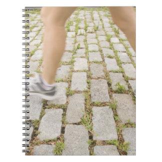 USA, New York City, Blurred legs of woman Notebooks