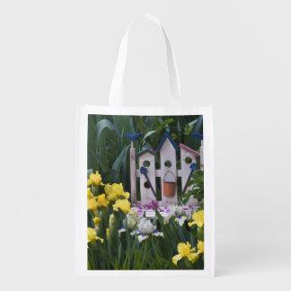 USA, Pennsylvania. Garden irises grow around Reusable Grocery Bag
