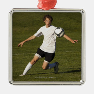 USA, Utah, Orem, teenage (14-15) boy playing Silver-Colored Square Decoration