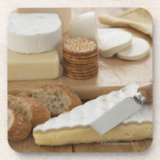 Various cheeses and bread on table drink coasters