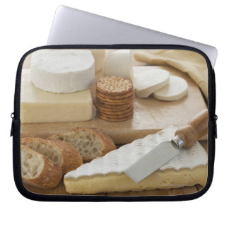 Various cheeses and bread on table laptop sleeve