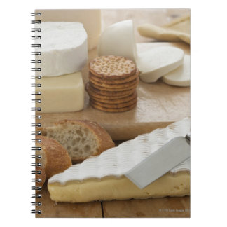 Various cheeses and bread on table notebooks