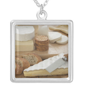 Various cheeses and bread on table silver plated necklace
