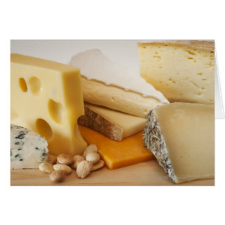 Various cheeses on chopping board greeting card