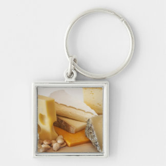 Various cheeses on chopping board Silver-Colored square key ring