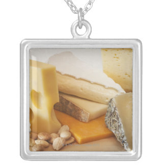 Various cheeses on chopping board silver plated necklace