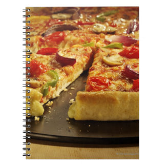 Vegetable pizza sliced on black pan on wood notebooks