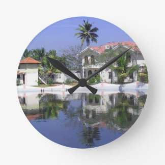 View of cottages and lagoon water in Alleppey Wall Clock