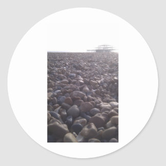 View over pebbles to silouetted West Pier Classic Round Sticker