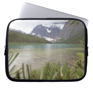 View past pine branches to mountain lake laptop sleeve