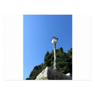 Vintage street lamp against blue sky postcard