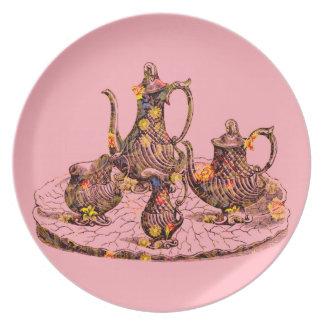 Vintage teapots on pink dinner/decorative plate