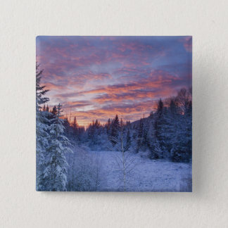 Vivid sunset paints the sky above wintery 15 cm square badge