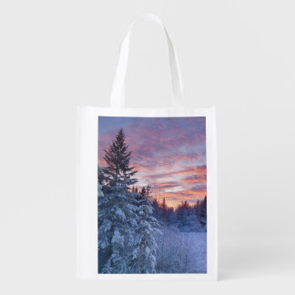Vivid sunset paints the sky above wintery reusable grocery bag