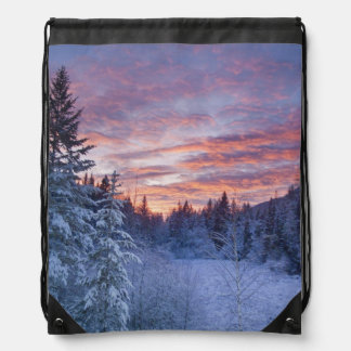 Vivid sunset paints the sky above wintery rucksacks