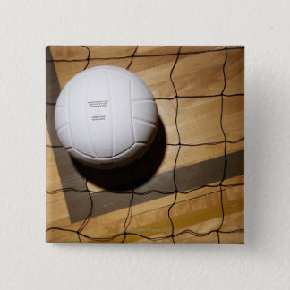 Volleyball and net on hardwood floor of 15 cm square badge