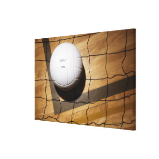 Volleyball and net on hardwood floor of stretched canvas print