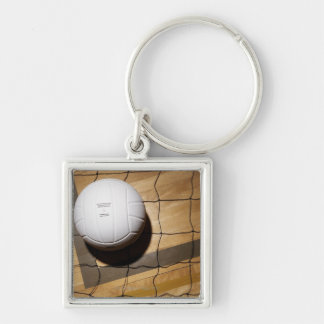 Volleyball and net on hardwood floor of Silver-Colored square key ring