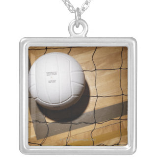 Volleyball and net on hardwood floor of silver plated necklace