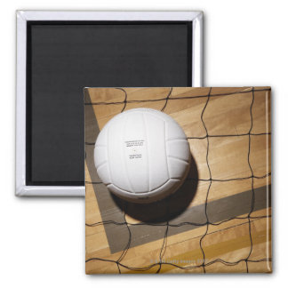 Volleyball and net on hardwood floor of square magnet
