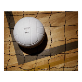 Volleyball and net on hardwood floor poster
