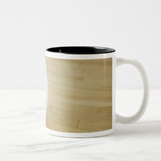Volleyball on wooden floor Two-Tone coffee mug