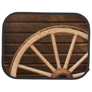 Wagon wheel leaning against old wooden wall car mat