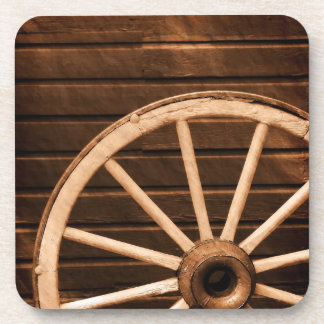Wagon wheel leaning against old wooden wall coaster