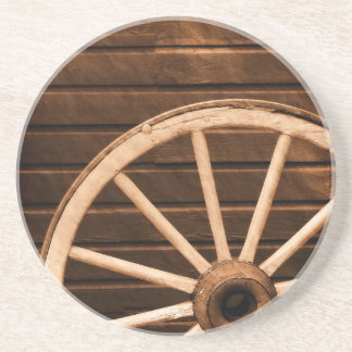Wagon wheel leaning against old wooden wall drink coasters