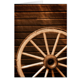 Wagon wheel leaning against old wooden wall greeting card