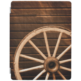 Wagon wheel leaning against old wooden wall iPad cover