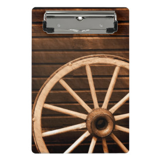 Wagon wheel leaning against old wooden wall mini clipboard
