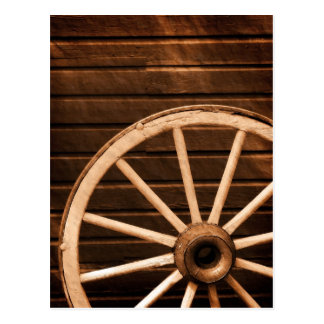 Wagon wheel leaning against old wooden wall postcard