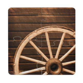 Wagon wheel leaning against old wooden wall puzzle coaster