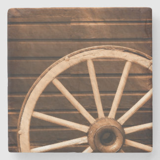 Wagon wheel leaning against old wooden wall stone coaster
