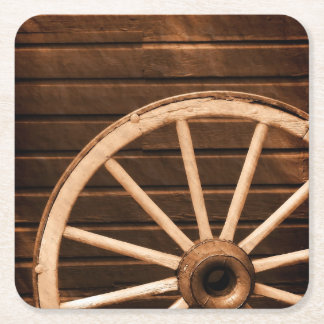 Wagon wheel leaning against old wooden wall square paper coaster