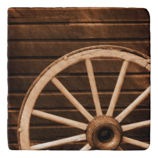 Wagon wheel leaning against old wooden wall trivet