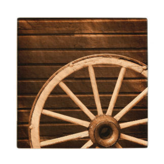Wagon wheel leaning against old wooden wall wood coaster