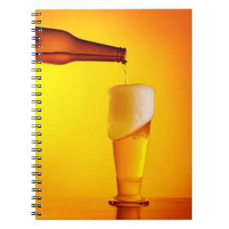 Waiter pouring beer, glass of a cold drink spiral notebooks